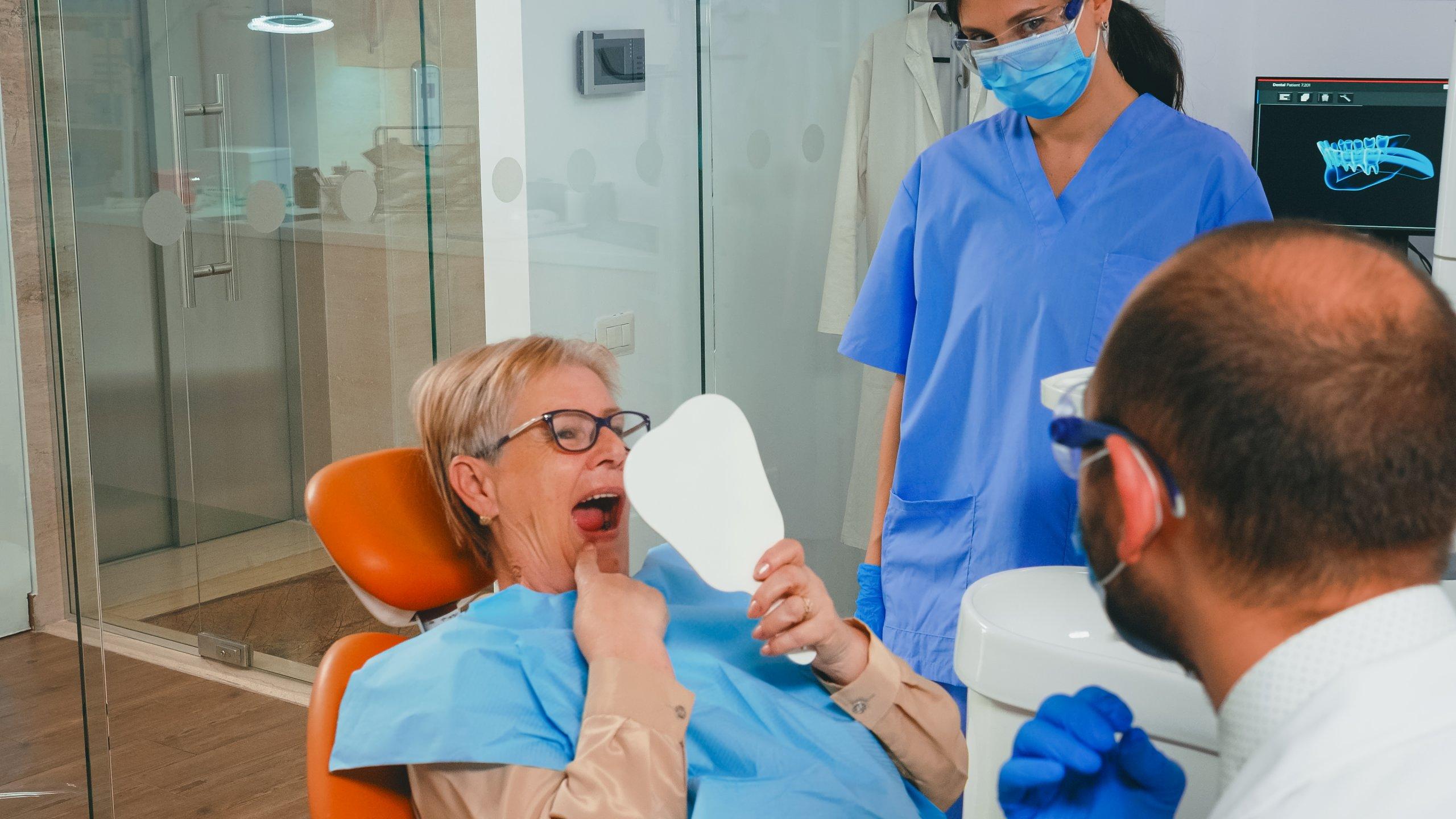 השתלת שיניים בגאורגיה - אישה מסתכלת במראה לאחר ניתוח